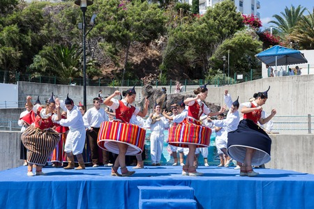 folk dance: MADEIRA, PORTUGAL - AUG 10: Dancers with local costumes demonstrating a folk dance on August 10, 2014 at the beach of Funchal, Madeira Island, Portugal Editorial