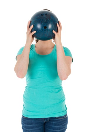 Woman is holding a bowling ball just before her head, isolated over white