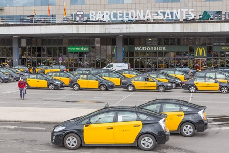 BARCELONA, SPAIN - MAY 16: Travelers and several taxis waiting in front of the railway station Barcelona-Sants on May 16, 2013 in Barcelona, Spain