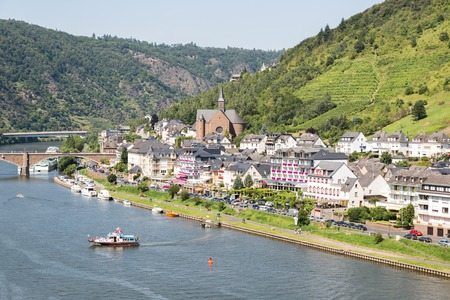moseltal: Aerial view of Cochem along river Moselle in Germany with a small ship crossing the river