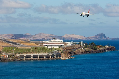 portugese: FUNCHAL, PORTUGAL - AUG 12: A Boeing 737 from Portugese airline TAP is approaching Funchal Airport on Augustus 12, 2014 at Madeira, Portugal