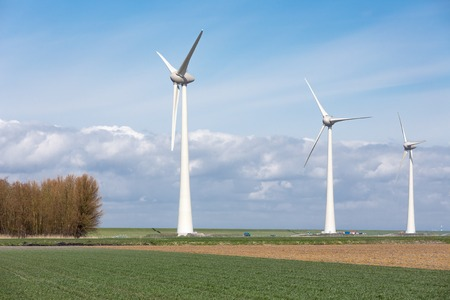 windfarm: Farmland with wind turbines of the biggest windfarm in the Netherlands. The axle height of these turbines is 135 meter and the wings have a peak height of almost 200 meter. Stock Photo