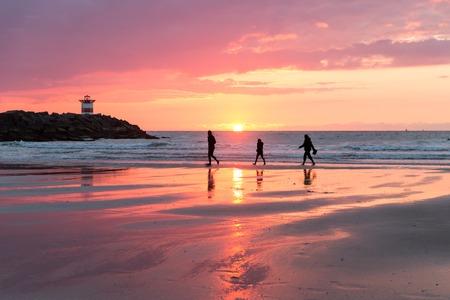Beautiful sea sunset at the Dutch coast near Scheveningen with passing walkers photo