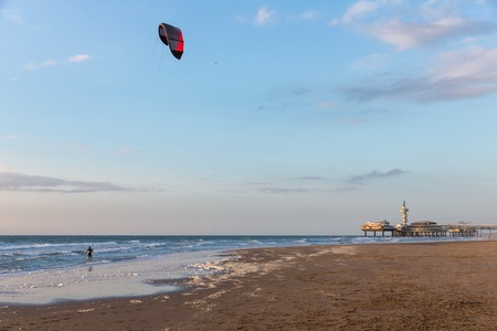 scheveningen: Kite surfing in the evening along the Dutch coast with a view at the famous Pier of Scheveningen