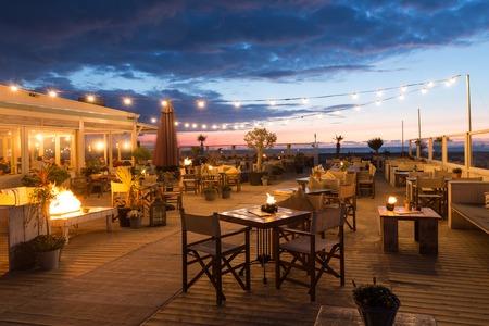 スケベニンゲン オランダ 4 月 30 日: 2015 年 4 月 30 日にオランダの海岸沿いのテラス付きのレストランで食べている人と海の夕日スケベニンゲン オラ