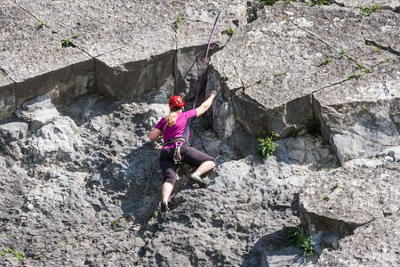 meuse: DINANT, BELGIUM - APR 30: Woman secured with ropes is climbing a vertical rock along the river Meuse on April 30, 2012 near Dinant, Belgium Editorial
