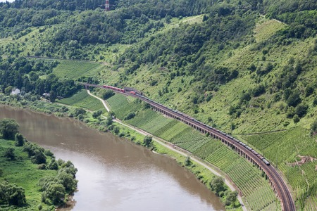 Aerial view of a passenger train and a freight train passing each other at a railway track along the river Moselle in Germany