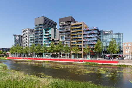 LELYSTAD THE NETHERLANDS JUNE 11: View at modern apartments and office buildings with a pond in front of it on June 11 2015 in Lelystad the Netherlands