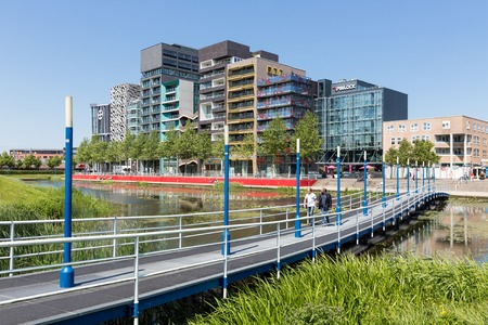 lelystad: LELYSTAD THE NETHERLANDS JUNE 11: View at modern apartments and office buildings with catwalk crossing a pond in front of it on June 11 2015 in Lelystad the Netherlands