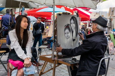 PARIS FRANCE May 28: Street artist is painting a beautiful woman at Place du Tertre in Montmartre one of the most touristic attractions of the city on May 28 2015 in Paris France Editorial