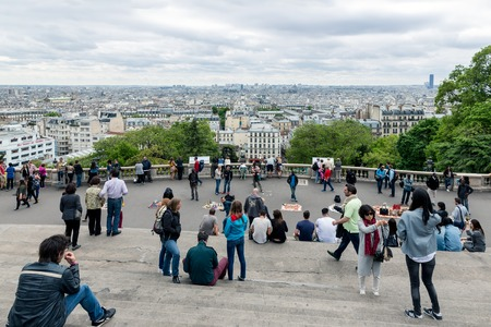admiring: PARIS FRANCE May 28: Tourists admiring the skyline of Paris from the stairs of the Sacre Coeur Basilica the highest point city of Paris on May 28 2015 Paris France Editorial