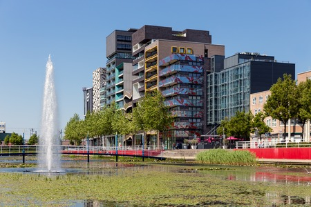 pond: View at modern apartments and office buildings with pond and fountain in front of it Lelystad the Netherlands