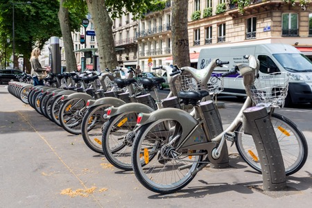 bycicle: PARIS, FRANCE - May 29: Streetview with unknown woman paying for renting a bycicle on May 29, 2015, Paris, France