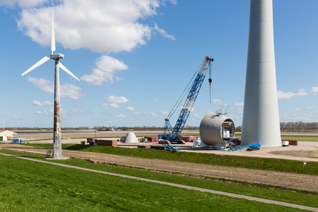 Dutch farmland with replacement of old wind tubines through enormous new wind turbines