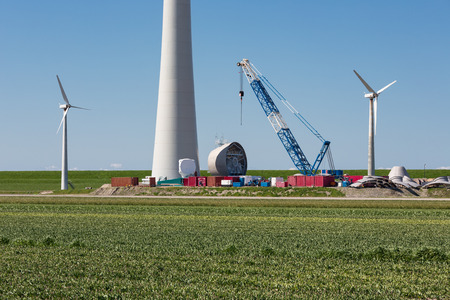 enormous: Dutch farmland with replacement of old wind turbines through enormous new wind turbines Stock Photo