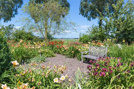 retreat: Beautiful Dutch blooming garden with a retreat and wooden bench Stock Photo