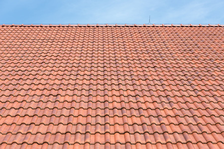 slate roof: Red tiles roof background with blue sky Stock Photo
