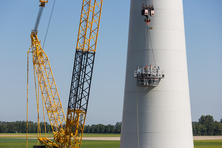 Dutch workers busy with the construction of a big new windturbine