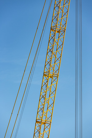 Detail yellow crane jib against a blue sky