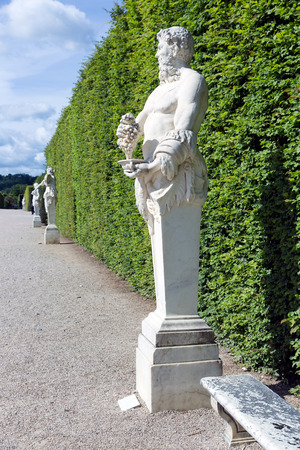 Footpath With Ornamental Statues In The Garden Of Palace Versailles Near  Paris, France Stock Photo