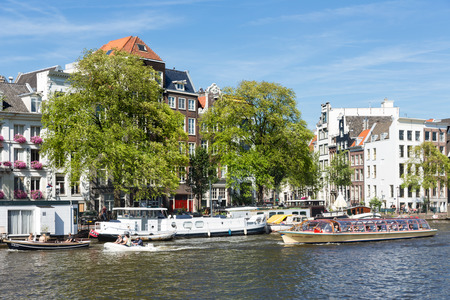 amstel river: AMSTERDAM, THE NETHERLANDS - AUG 06: Canal with recreating people in small boats and a passing cruise ship on August 06, 2015 downtown in Amsterdam, capital city of The Netherlands Editorial