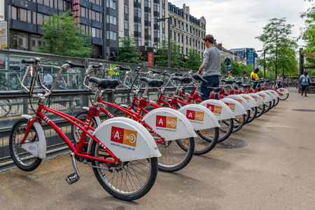 shared: ANTWERP, BELGIUM - AUG 11: Man is parking a bicycle at an automatic bicycle rental for shared bicycles on August 11, 2015 in Antwerp, Belgium