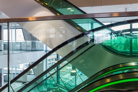 green office: Escalators with green illumination in modern office building