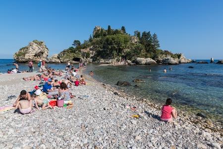 taormina: TAORMINA, ITALY - MAY 21: Tourists relaxing at the beach of Taormina on May 21, 2016 at the island Sicily, Italy