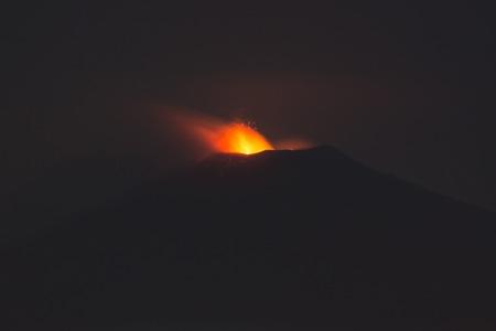 erupting: Eruption of Sicilian volcano Etna at night, seen from Taormina at 15 kilometre away. Stock Photo