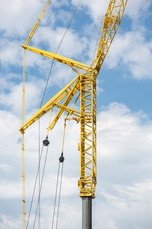 Large yellow telescopic crane against cloudy sky