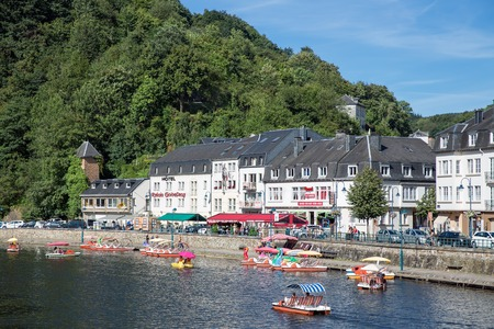 the ardennes: BOUILLON, BELGIUM - AUG 13: Belgian medieval city along river Semois  in Ardennes with tourists relaxing in paddle boats on August 13, 2016 in Bouillon, Belgium