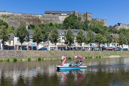 BOUILLON, BELGIUM - AUG 13: Belgian medieval city with castle and people relaxing in pedalo at river Semois on August 13, 2016 in Bouillon, Belgium Editorial