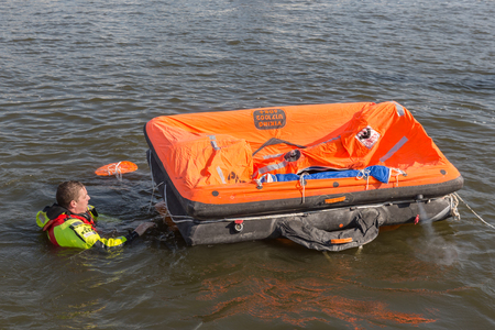 URK, THE NETHERLANDS - SEP 24: Rescue worker showing how to use a life raft on September 24, 2016 in the harbor of Urk, the Netherlands