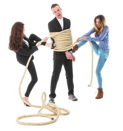 venganza: Dos mujer enojada atar un hombre de negocios con una cuerda, aislado en un fondo blanco