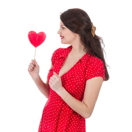 Beautiful woman in red dress eagers a red heart-shaped lollipop in front of her isolated on white Stock Photo
