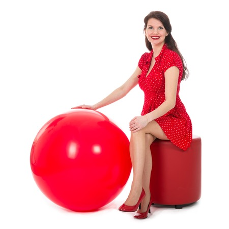 the footstool: Beautiful woman in red dress sitting on footstool holding a big red balloon; isolated on white background Stock Photo