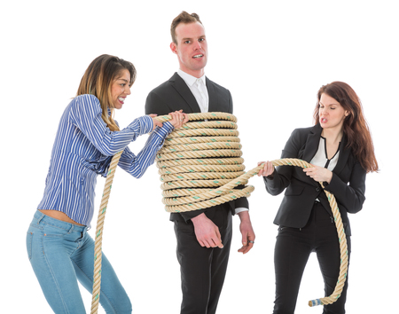 Two angry woman tying a business man with rope, isolated on a white background Stock Photo