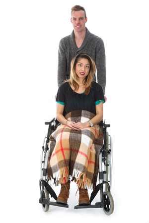 Man pushing woman in a wheelchair isolated on white background