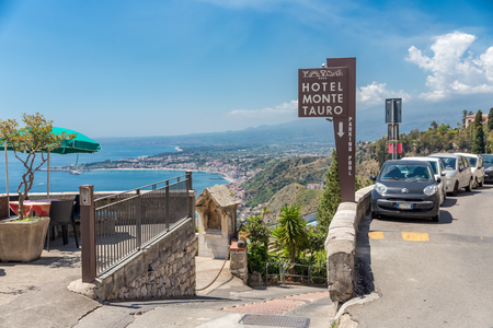 ortseingangsschild: TAORMINA, ITALY - MAY 17, 2016: Entrance to a four star hotel in Taormina with a beautiful view at the Sicilian coast with the Etna