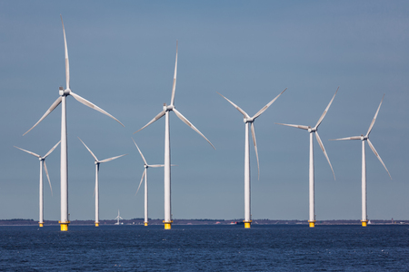 Offshore farm windturbines near Dutch coast against blue sky