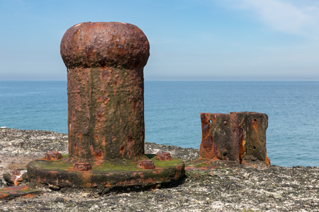 Old decayed and rusty bollard at Dune, small island near Helgoland in German Northsea Stock Photo