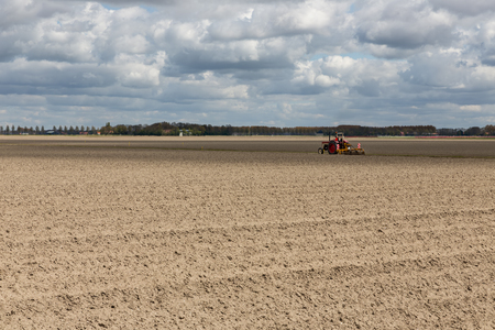 agrarian: Dutch landscape with tractor in stripes of plowed field in early spring