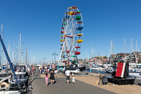 local 27: URK, THE NETHERLANDS - MAY 27, 2017: Ferris wheel at harbor of Urk during a local fishing day event