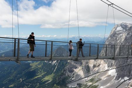 DACHSTEIN MOUNTAINS,  AUSTRIA - JULY 17, 2017: Dachstein Mountain in Austria with hikers passing a skywalk rope bridge