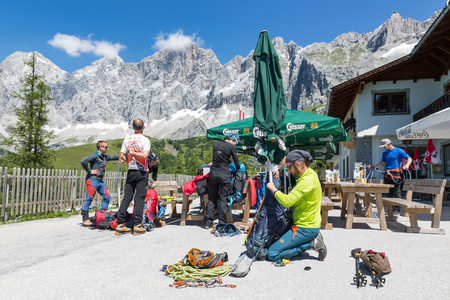 DACHSTEIN MOUNTAINS,  AUSTRIA - JULY 17, 2017: Alpinists preparing their equipment for rock-climbing in Dachstein Mountains of Austria