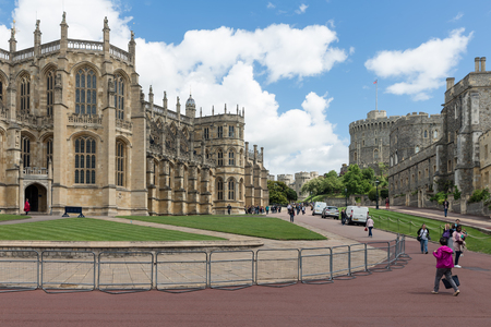 old english: WINDSOR, ENGLAND - JUNE 09, 2017: People visiting Windsor Castle with St Georges chapel. Windsor Castle is the family home to British kings and queens for over 1,000 years.