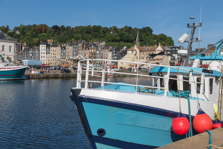 Wooden fishing ship in Harbor Honfleur with bright sun, France