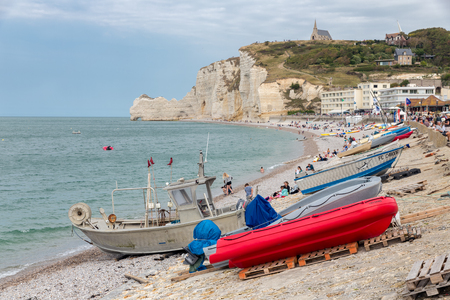 ETRETAT, FRANCE - AUGUST 25, 2017: Fishing boats and seaside visitors at the beach near the cliffs of Etretat in Normandie, France