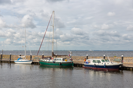 Harbor of historic Dutch village Urk with modern sailing yachts moored to a pier Stock Photo