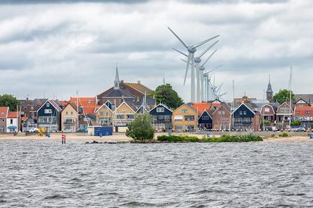 Zeegezicht Nederlands vissersdorpje Urk met grote windturbines die boven de skyline van de huizen uitkomen Stockfoto - 89729625